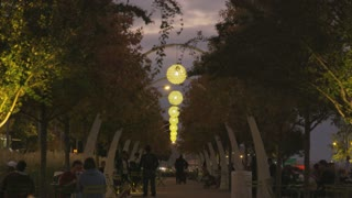 Couple Walks through Lit Archways in the Evening in Dallas Park
