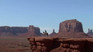 Cowboy And His Horse Stand On A Cliff In Monument Valley