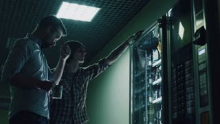 coworkers choosing food in vending machine at night office building