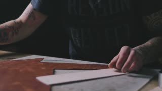 Craftsman's hands cutting a piece of leather on the table with a knife, dolly shot, close up