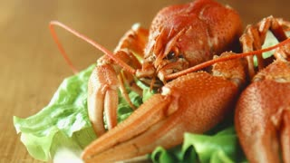 Crayfish lobsters on a tray with a green lettuce leaf, close shot