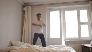 Crazy teenager jumps on the bed. Time lapse. Wide shot.