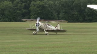 Cream Colored Plane Taxiing on Grass Field