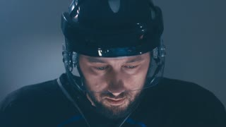 CU Caucasian male ice hockey player in black uniform preparing for the game. 4K UHD 60 FPS slow motion. RAW edited footage