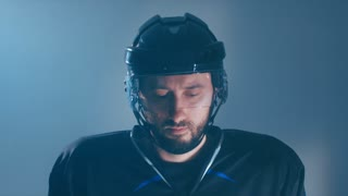 CU Portrait of Caucasian male ice hockey player in black uniform, looking into the camera. 4K UHD 60 FPS slow motion. RAW edited footage