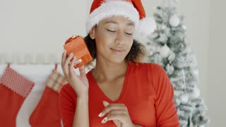 Curious young woman shaking her Christmas gift
