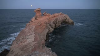 Curved Rock, Ocean, and Moon in Sky 2