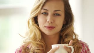Cute blond girl holding cup of drink and smiling at camera