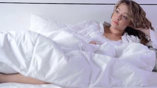 cute blond woman in lifestyle scene in white bedroom
