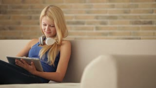 Cute blonde girl wearing headset relaxing on couch using touchpad looking at camera and smiling