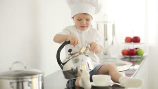 Cute boy pours tea from a teapot