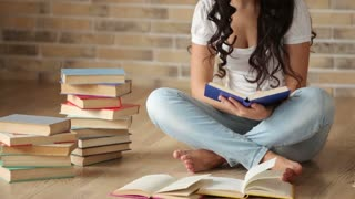 Cute brunette girl sitting on floor reading book and smiling at camera