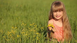 Cute child sitting on grass with flowers