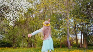 Cute girl 7-8 years old with blond long hair with wreath of dandelions on the head running and spinning in the park. Slow motion from Sony A6300