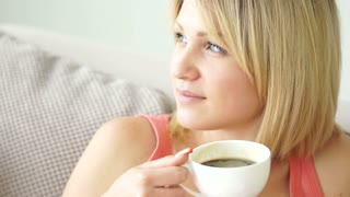 Cute girl drinking coffee and looking out the window