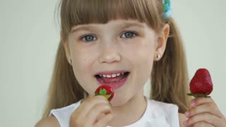 Cute girl eating strawberry and laughing