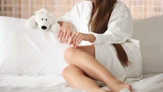 Cute girl in bath robe sitting on bed looking at camera and smiling. Panning camera