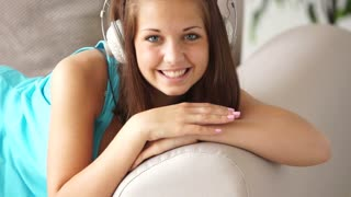 Cute girl in headset relaxing on sofa and smiling at camera