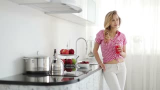 Cute girl in kitchen holding glass of juice and smiling at camera