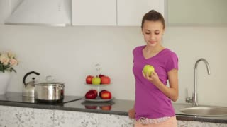 Cute girl is standing in the kitchen and eating an apple