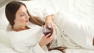 Cute girl lying in bed holding glass of wine looking at camera and smiling