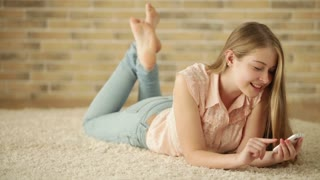Cute girl lying on carpet using mobile phone looking at camera and smiling. Panning camera