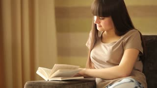 Cute girl reading and looking at camera with smile