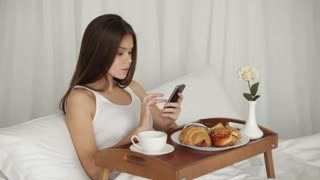 Cute girl relaxing in bed using mobile phone drinking from cup looking at camera and smiling