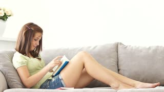 Cute girl relaxing on sofa reading book smiling and laughing