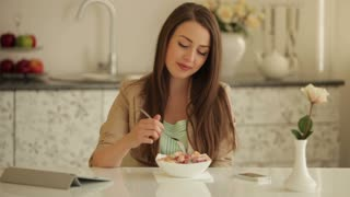 Cute girl sitting at kitchen table eating fruit salad and looking at camera with smile