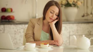 Cute girl sitting at kitchen table using mobile phone and eating cake
