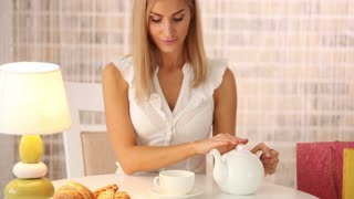 Cute girl sitting at table at cafe pouring tea into cup looking at camera and smiling. Panning camera