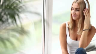 Cute girl sitting by window listening to music with headphones looking at camera and smiling. Panning camera