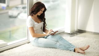 Cute girl sitting by window using touchpad and smiling at camera