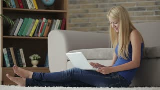 Cute girl sitting on carpet using laptop looking at camera and smiling