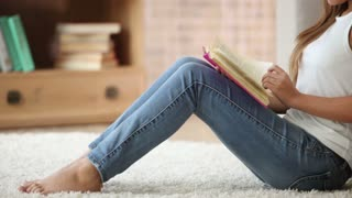 Cute girl sitting on floor reading book closing it and smiling. Panning camera
