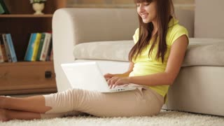 Cute girl sitting on floor using laptop closing it and smiling