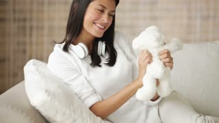Cute girl sitting on sofa playing with teddy bear looking at camera laughing and smiling. Panning camera
