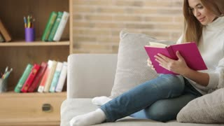 Cute girl sitting on sofa reading book closing it looking at camera and smiling. Panning camera