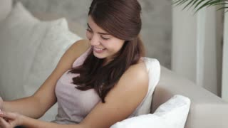Cute girl sitting on sofa using mobile phone looking at camera and smiling. Panning camera