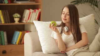 Cute girl sitting on sofa with headset eating apple and smiling at camera
