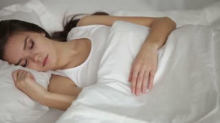 Cute girl sleeping in bed smiling and moving in her sleep. Panning camera