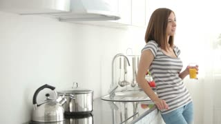 Cute girl standing in kitchen and drinking fresh juice