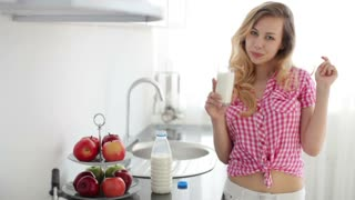 Cute girl standing in kitchen drinking milk and laughing at camera