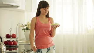 Cute girl standing in kitchen eating fruits and smiling