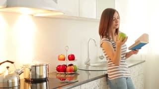 Cute girl standing in kitchen reading book and eating apple