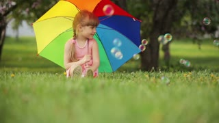 Cute girl with colorful umbrella smiling