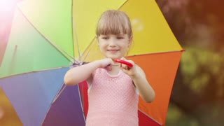 Cute girl with umbrella smiling. Lens flare and sunlight