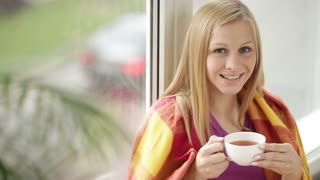 Cute girl wrapped in plaid blanket sitting by window drinking tea looking at camera and smiling