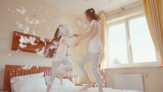 Cute girls jumping and spinning on the bed. Among the fluff and feathers. Slowmotion